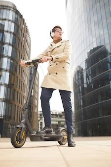 Verticale volledige lengte laag portret van moderne jonge zakenman elektrische scooter rijden en wegkijken terwijl u luistert naar muziek met gebouwen van de stedelijke stad op de achtergrond, kopie ruimte