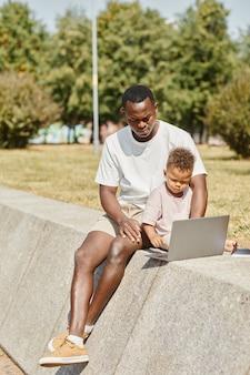 Verticale volledige lengte portret van jonge afro-amerikaanse man met behulp van laptop buitenshuis met schattige zoontje