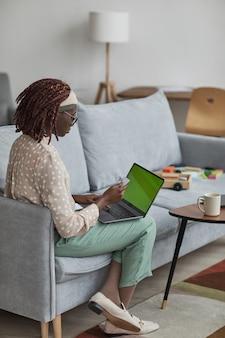 Verticale volledige lengte portret van jonge afro-amerikaanse vrouw die laptop met groen scherm gebruikt en creditcard vasthoudt terwijl ze thuis op de bank zit, kopieer ruimte