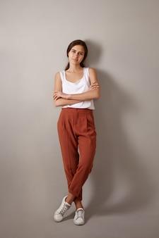 Verticale volledige lengte trendy ogende modieuze jonge europese vrouw gekleed in witte top, bruine broek en sneakers poseren geïsoleerd, armen oversteken vol vertrouwen, genieten van vrije tijd