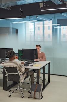 Verticale volledige lengte van it-programmeurs of studenten die computers gebruiken in een kantoorinterieur met glazen wand, kopieerruimte