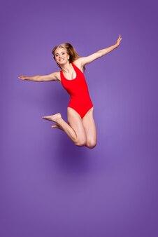 Verticale volledige lengte van vrolijke dame springen op paars helder levendig