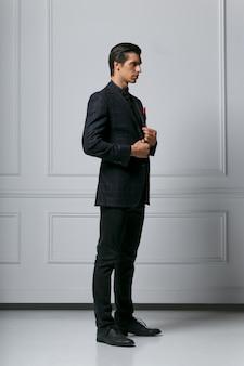 Verticale weergave. elegante jonge mode man die zijn pak aanpast terwijl hij naar zijn kant kijkt, op een witte achtergrond.