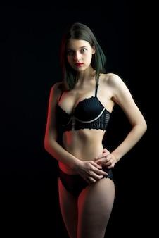 Verticale weergave foto mooie verlegen dame in boudoir beha slipje kant bikini. inschrijving magere slanke vorm geïsoleerde zwarte muur