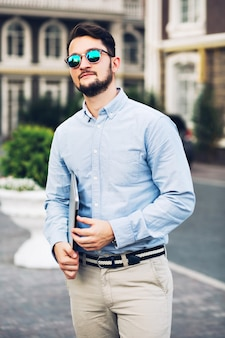 Verticale weergave knappe bebaarde zakenman in zonnebril britse wijk rondlopen.
