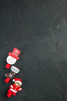 Verticale weergave van accessoires voor nieuwjaarsdecoratie op een rij aan de rechterkant op een zwart oppervlak