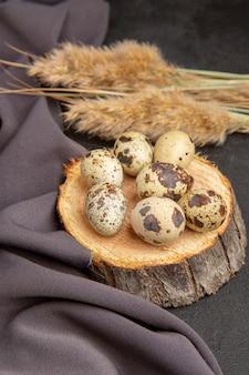 Verticale weergave van biologische eieren op een houten plank spike zwarte handdoek op donkere achtergrond