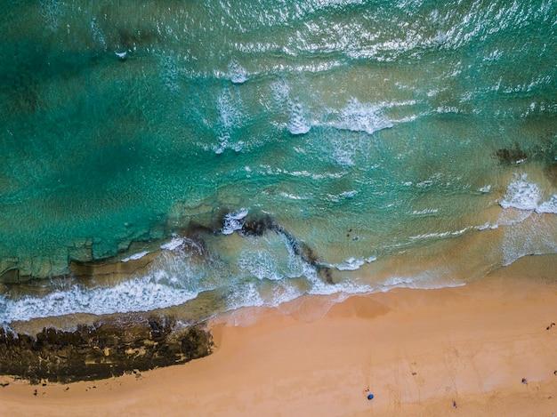 Verticale weergave van blauw schoon zeewater en geel zandstrand - concept van tropische schilderachtige plaats en zomervakantie vakantie - toerisme en toeristen mensen