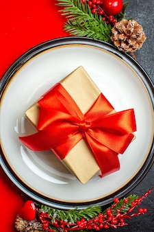 Verticale weergave van borden met cadeau erop en dennentakken met decoratie accessoire conifer kegel op een rood servet