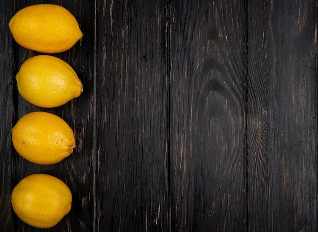 Verticale weergave van citroenen aan de linkerkant en zwarte achtergrond met kopie ruimte