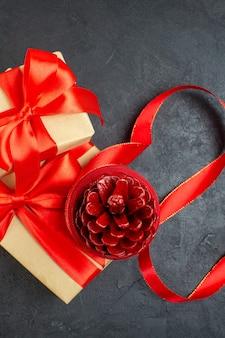 Verticale weergave van conifer kegel op mooi cadeau op donkere achtergrond