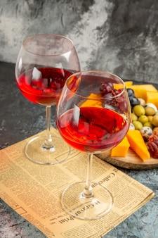 Verticale weergave van de beste snack en twee glazen droge rode wijn op een oude krant op een grijze achtergrond
