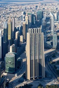 Verticale weergave van dubai stad vanaf de top van een toren.