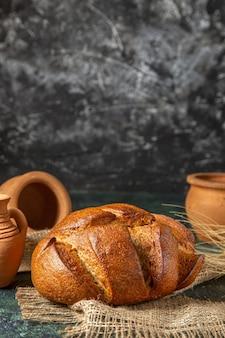 Verticale weergave van een brood van dieet zwart brood op bruine handdoek en pottenbakkerijen op donkere kleuren oppervlak