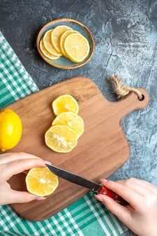 Verticale weergave van een hand die verse citroenen hakt op een houten snijplank op een donkere achtergrond