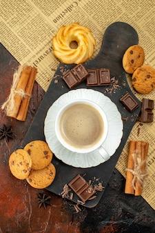 Verticale weergave van een kopje koffie op een houten snijplank op een oude krant, koekjes, kaneellimoenen, chocoladerepen op een donkere achtergrond