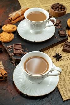 Verticale weergave van een kopje koffie op een houten snijplank op een oude krant, koekjes, kaneellimoenen, chocoladerepen