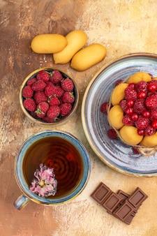Verticale weergave van een kopje warme kruidenthee zachte cake met fruit chocoladerepen op gemengde kleurentafel