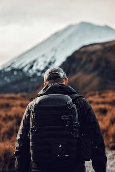 Verticale weergave van een man in het zwart met een rugzak wandelen in de buurt van de prachtige bergen