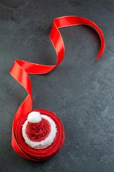 Verticale weergave van een rol rood lint met kerstman hoed erop op donkere achtergrond