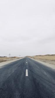 Verticale weergave van een smalle weg in het midden van het veld onder de heldere hemel