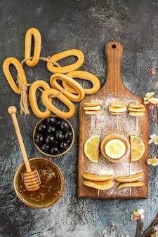 Verticale weergave van fruit pannenkoeken koekjes in de buurt van honing in een kom en zwarte kersen op grijze tafel