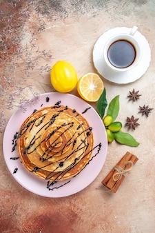 Verticale weergave van gemakkelijke pannenkoeken versierd met chocoladesiroop met lemonnd thee op kleurrijke tafel