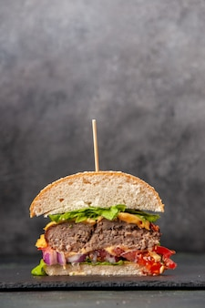 Verticale weergave van gesneden smakelijke sandwiches op zwarte lade op donkere mix kleur oppervlak