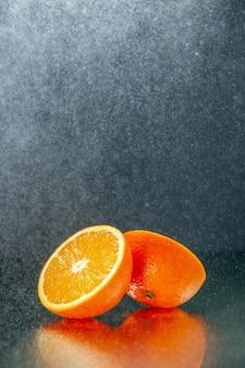 Verticale weergave van gesneden verse sinaasappels die naast elkaar staan op licht op zwarte achtergrond met vrije ruimte