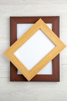 Verticale weergave van gestapelde kleine en grote lege afbeeldingsframes op witte houten