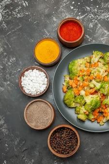 Verticale weergave van gezonde maaltijd met brocoli en wortelen op een zwarte plaat en kruiden op grijze tafel