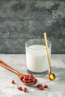 Verticale weergave van glazen beker gevuld met melk en pinda's in lepel op grijze achtergrond