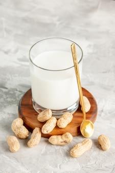 Verticale weergave van glazen beker gevuld met melk op houten dienblad en lepel van droog fruit op witte achtergrond