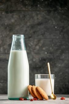Verticale weergave van glazen fles beker gevuld met melk en pinda's op grijze tafel op houten achtergrond