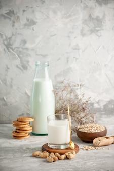 Verticale weergave van glazen fles en beker gevuld met melk op houten dienblad en droge vruchten gestapelde koekjes, lepel haver in bruine pot aan de linkerkant op witte tafel op ijsachtergrond