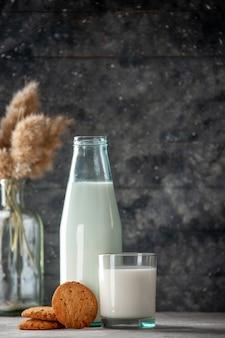 Verticale weergave van glazen fles en beker gevuld met melkkoekjes op donkere achtergrond