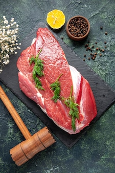 Verticale weergave van groen op vers rood rauw vlees bestek op snijplank en peper citroen houten hamer op groen zwart mix kleur achtergrond