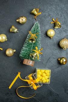 Verticale weergave van hand met decoratie accessoire geschenkdozen en kerstboom op donkere achtergrond