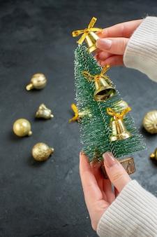 Verticale weergave van hand met kerstboom en decoratie accessoires op donkere achtergrond