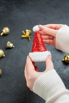Verticale weergave van hand met kerstman hoed en decoratie accessoires op donkere achtergrond