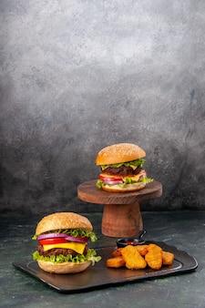 Verticale weergave van heerlijke broodjes frietjes kipnuggets op zwarte snijplank frietjes peper op donkere mix gekleurde wazig oppervlak