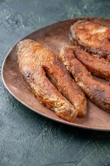 Verticale weergave van heerlijke gebakken vis op een bruine plaat op de tabel met mixkleuren met vrije ruimte