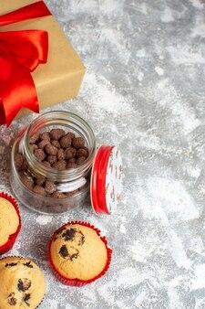 Verticale weergave van heerlijke kleine cupcakes en chocolade in een glazen pot naast cadeau met rood lint op ijsoppervlak
