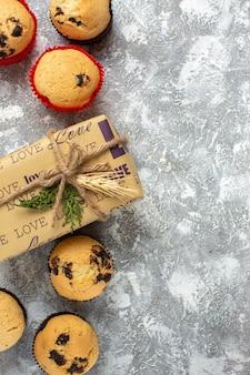 Verticale weergave van heerlijke kleine cupcakes met chocolade en dennentakken naast cadeau op ijsoppervlak