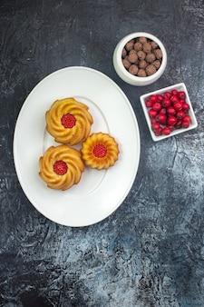 Verticale weergave van heerlijke koekjes op een witte plaat en cornelchocolade in kommen donker oppervlak