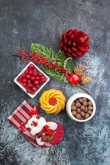 Verticale weergave van heerlijke koekjesdecoratie-accessoire santa claus sok en cornell in een kom dennentakken op een donkere ondergrond