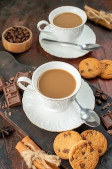 Verticale weergave van heerlijke koffie in witte kopjes op houten snijplankkoekjes, kaneellimoenen, chocoladerepen