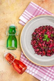 Verticale weergave van heerlijke salade met rode biet en boon en gevallen twee olieflessen op roze gestripte handdoek op gemengde kleur achtergrond