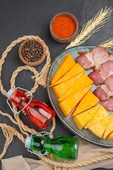Verticale weergave van heerlijke snacks gevallen flessen, paprika's op handdoek en touw op een zwarte achtergrond