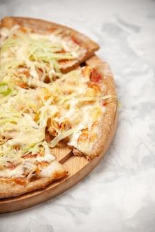 Verticale weergave van heerlijke veganistische pizza verdeeld in kwarten op witte ondergrond